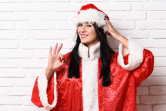 Pretty cute sexy santa girl. Or smiling brunette woman in red sweater with christmas or xmas hat and showing ok on white brick wall background Royalty Free Stock Photos