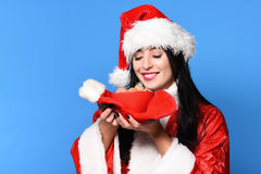 Pretty cute sexy santa girl. Or smiling brunette woman in red sweater and new year hat holds decorative christmas or xmas stocking or boot and chocolate ?hip Royalty Free Stock Photo