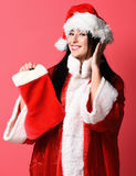 Pretty cute sexy santa girl. Or smiling brunette woman in red sweater and new year hat holds decorative christmas or xmas stocking or boot on studio background Stock Photos