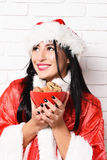 Pretty cute sexy santa girl. Or smiling happy brunette woman in new year sweater and hat holds christmas or xmas chocolate ?hip cookies in bowl on white brick Stock Photo