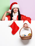 Pretty cute sexy santa girl. Or smiling woman in red sweater and new year hat holds decorative christmas or xmas bucket with colorful balls and stocking or boot Stock Image