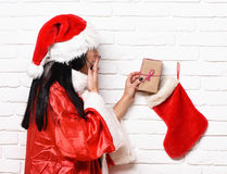Pretty cute sexy santa girl. Or surprised brunette woman in new year sweater and christmas or xmas hat gets present from stocking or boot on white brick wall Royalty Free Stock Photo
