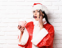 Pretty cute sexy santa girl. Or surprised brunette woman in new year sweater and christmas or xmas hat holds pink piggy pig bank on white brick wall background Royalty Free Stock Image