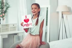 Pretty cute small Afro-American girl holding I love mom sign. royalty free stock photography