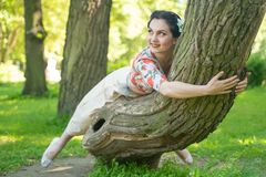 Pretty cute young brunette woman posing with her lovely tree in the green summer garden alone. happy girl pleasure in the nature, royalty free stock photos