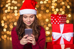 Pretty cute young female in santa claus hat using smartphone Stock Photos