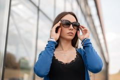 Pretty cute young hipster woman in stylish sunglasses in a fashionable vintage t-shirt in a vintage blue knitted cape