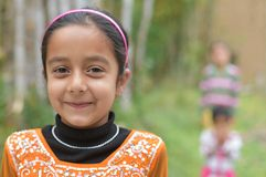 Pretty Cute young Indian girl child smiling with soft green natural backdrop. Cute young Indian girl smiling with soft green natural backdrop Stock Image