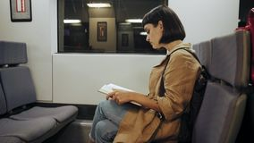 Activity in train. Pretty cute young woman in hipster coat sits in midnight express train on her way back home in commuting hours, she reads book, looks out of stock video footage