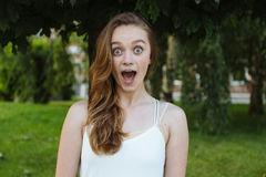 Pretty cute young woman surprised shocked on green background. Real people expression Royalty Free Stock Image