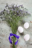 Pretty dainty rustic Easter background. With a posy of delicate blue purple blossoms and three natural white boiled hens eggs on old textured weathered wood stock photos
