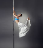 Pretty dancer bent elegantly while dancing on pole Royalty Free Stock Photos