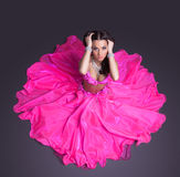 Pretty dancer in pink costume sitting on floor Stock Images