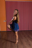 Pretty Dancer Standing on Tip Toe with One Foot. Pretty Young Dancer in Blue Dress Standing on Tip Toe with One Foot and Smiling at the Camera Inside the Studio stock photography
