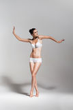 Pretty dancing ballerina in white studio Stock Photos