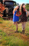 Pretty Dancing Country Girls. Two happy teenage country girls with long brown hair, dancing and laughing in front of a rusty old truck. Shallow depth of field Stock Photo
