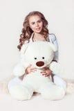 Pretty dark blonde girl hugging teddy bear. Pretty dark blonde girl wearing in wight clothes hugging teddy bear on white background. Image released Royalty Free Stock Image