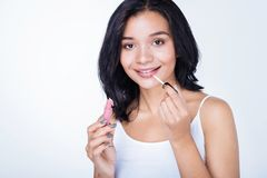 Pretty dark-haired woman applying lip gloss. Shiny lips. Beautiful dark-haired young woman in a white tank top applying pink lip gloss to her lips while standing Royalty Free Stock Photography