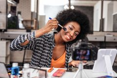 Pretty dark-skinned woman with bright makeup feeling amused. Stylish makeup. Pretty dark-skinned woman with bright makeup feeling amused while putting blusher on stock image
