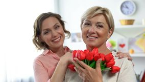 Pretty daughter and mom with tulips smiling at camera, mothers day celebration. Stock photo stock image