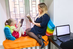 Pretty daughter with young mother read books on sill stock image