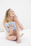 Pretty day dreaming blonde sitting on bed using tablet Stock Images