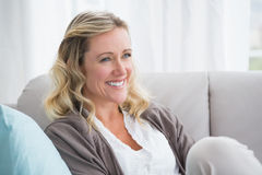 Pretty day dreaming blonde sitting on the couch Stock Photo