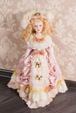 Antique doll in beautiful clothes. Pretty delicate antique doll with long blonde ringlets dressed in a beautiful pink nineteenth century gown and accessories Royalty Free Stock Image