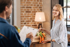 Pretty delighted lady examining contents of the box Royalty Free Stock Image