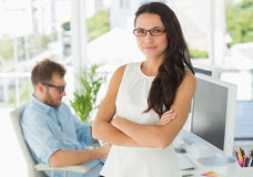 Pretty designer looking at camera leaning on desk Stock Image