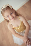 Pretty diligent ballet girl sitting in white tutu at dance studio. Alone royalty free stock photography