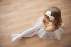 Pretty diligent ballet girl sitting in white tutu at dance studi Royalty Free Stock Image
