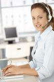 Pretty dispatcher working in bright office smiling. Pretty dispatcher working in office, using headset and laptop, smiling Stock Photos