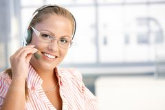 Pretty dispatcher working smiling. Pretty dispatcher working in office, using headset, smiling royalty free stock photography