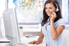 Pretty dispatcher working smiling. Pretty dispatcher working in office, smiling, looking at screen Royalty Free Stock Images