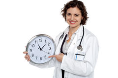 Pretty doctor pointing out time on wall clock Royalty Free Stock Photography