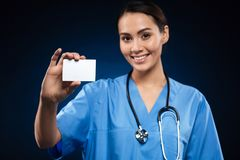 Pretty doctor showing blank badge and smiling isolated stock photos