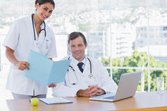 Pretty doctor showing a folder to a colleague Stock Image