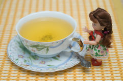 Pretty doll beside cup of green tea. Pretty little doll standing beside the gold painted handle of a cup of green tea on on a yellow table cloth stock photo
