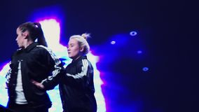 Pretty dynamic girls in black sportive clothes perform on stage at festival. Group of dynamic attractive girls wearing black sport clothes synchronically and stock footage