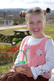 Pretty Easter Girl. Pretty young girl in pink holding small Easter basket Stock Photo