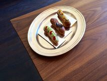 Pretty eclairs on a silver tray on a wooden table. Three pretty eclairs/pastries - pistachio-cherry, chocolate-hazelnut and passionfruit-chocolate - served on a Royalty Free Stock Images