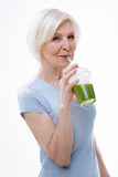 Pretty elderly woman drinking smoothie Royalty Free Stock Photo