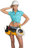 Pretty electrician in helmet, shorts, shirt, tool Stock Images
