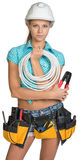 Pretty electrician in helmet, shorts, shirt, tool Royalty Free Stock Image