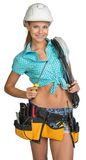 Pretty electrician in helmet, shorts, shirt, tool Royalty Free Stock Photography