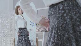 Pretty elegant mature woman looking in the mirror, examining her reflection. The lady looking at her new long skirt in