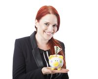 Pretty elegant redhead woman with a piggy bank Stock Images