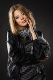 Pretty elegant woman in black leather jacket. Portrait of a pretty elegant woman in leather jacket over black background Stock Photo