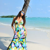 Pretty elegant woman in colorful dress relaxing on a beach Royalty Free Stock Photography